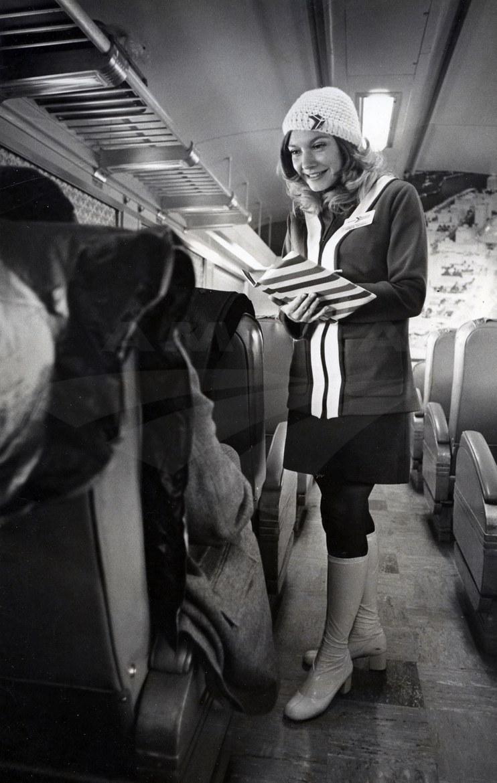Passenger service representative talking with passengers, 1970s.
