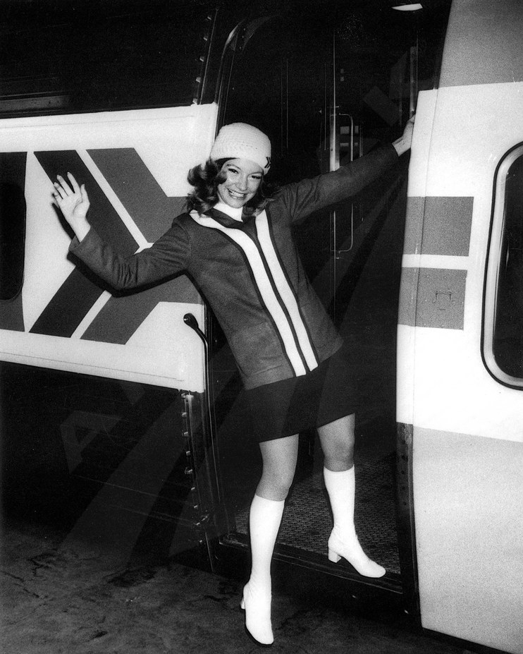 Passenger service representative waving, early 1970s.