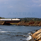 Train moving along the edge of a waterway, 1980s.