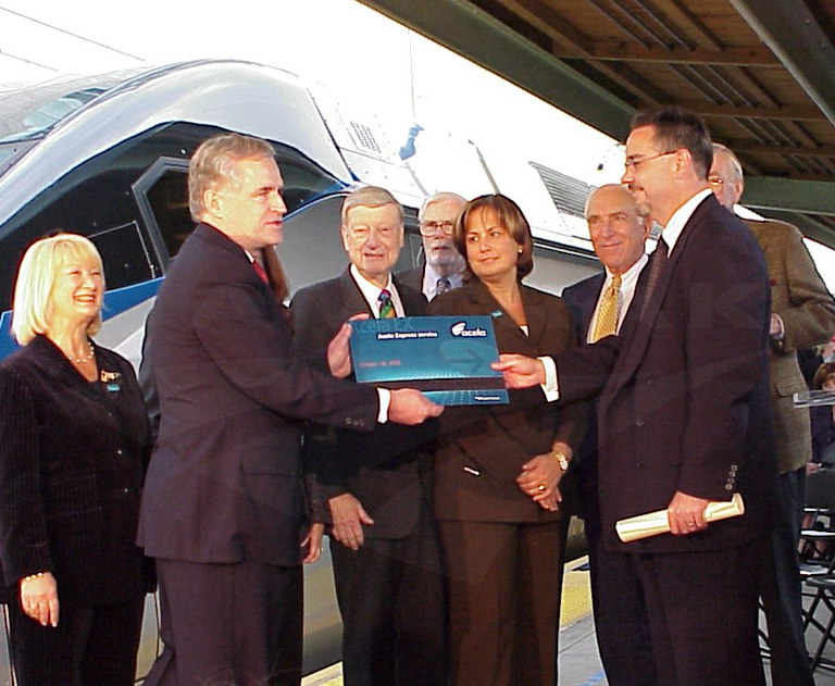 Richard Sarles, NEC vice president of High-Speed Rail, presents George Warrington with an oversized version of the key card that starts Acela Express, 2000