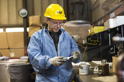 Sheet metal worker Steve Osburn applies teflon paste to airbrake components.