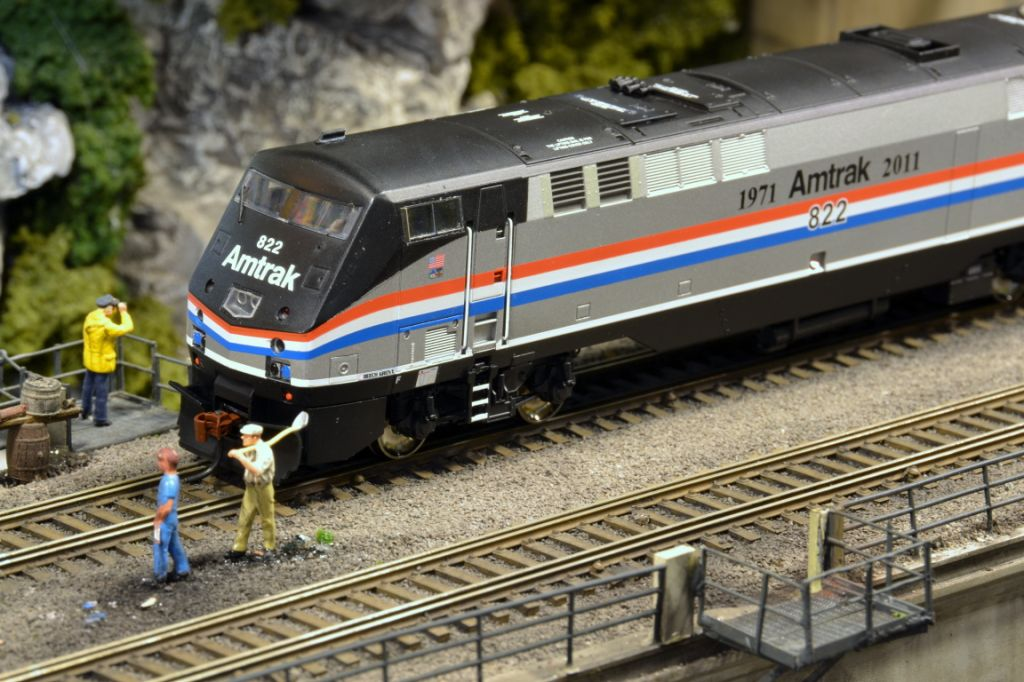 Some model railroad employees clean up the right-of-way before the photo shoot starts.